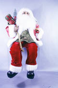 30CMH SITTING SANTA IN RED/GOLD HOLDING  A NUTCRACKER & GIFT
